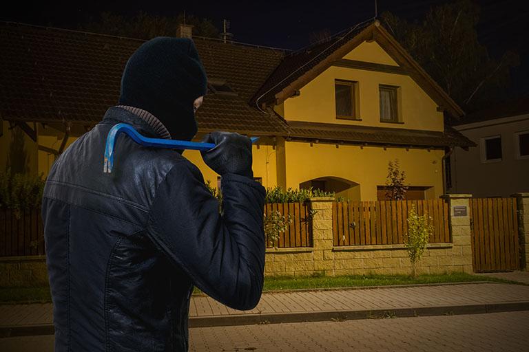 Einbrecher steht vor dem Haus bei Nacht
